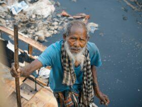 elderly ethnic man near dirty river