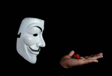 photo of guy fawkes mask with red flower on top on hand