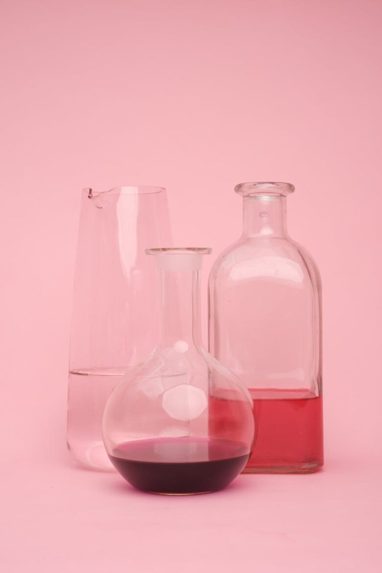 laboratory test tube with various liquids on pink surface