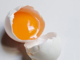 broken uncooked egg on white table