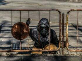 person wearing gas mask sitting behind metal fence